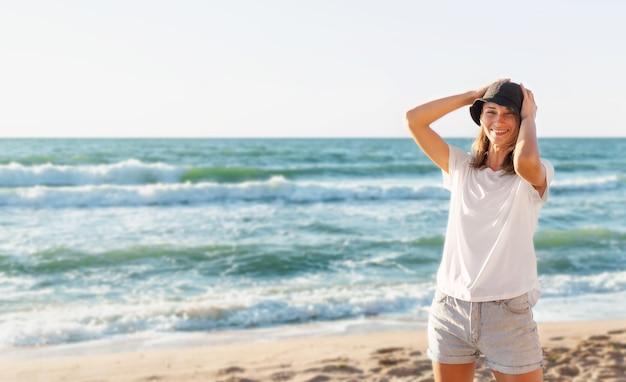 Porträt der glücklichen schönen jungen frau, die am strand bei sonnenuntergang steht. positive stimmung, sommerferien, sonniges konzept