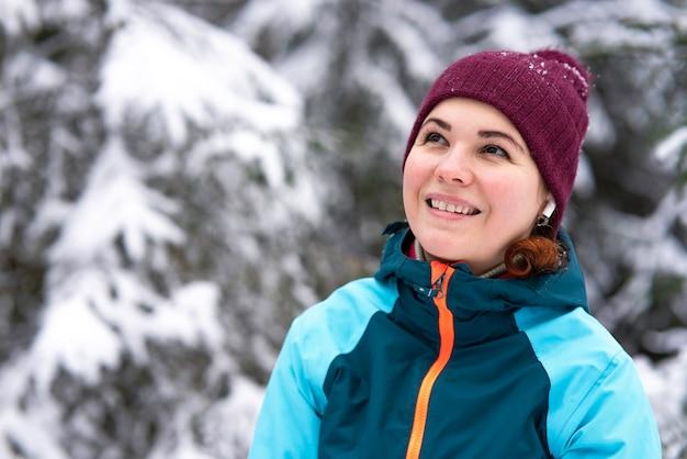 Porträt der glücklichen schönen jungen frau, die in einem schneebedeckten winterwald lächelt