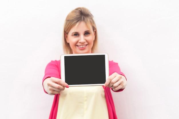 Porträt der glücklichen schönen jungen geschäftsfrau in der rosa bluse, die leeren bildschirm der tablette mit zahnigem lächeln steht und hält und kamera betrachtet. innen, isoliert, kopienraum, weißer hintergrund