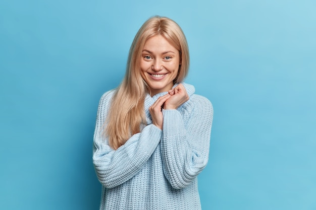 Porträt der glücklichen schüchternen jungen frau hält hände zusammen sieht positiv aus, trägt lässig gestrickten pullover posiert gegen blaue wand
