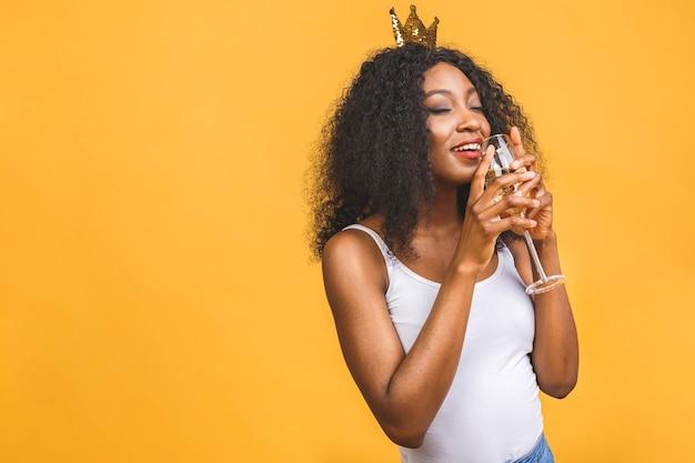 Porträt der glücklichen schwarzen afroamerikanischen frau mit glas champagner und goldener krone