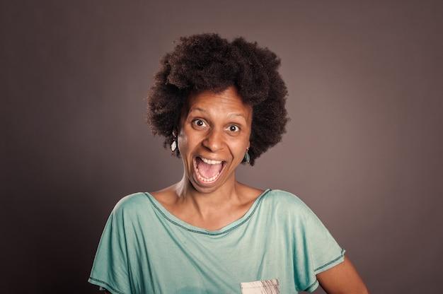 Porträt der glücklichen schwarzen frau, die auf grau lächelt
