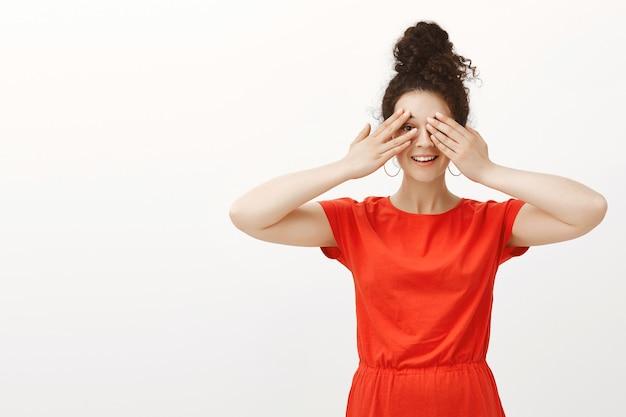 Porträt der glücklichen sorglosen kaukasischen frau mit dem lockigen haar im stilvollen roten kleid, das augen mit handflächen bedeckt und fröhlich lächelt