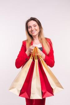 Porträt der glücklichen stilvollen jungen frau mit einkaufstaschen im roten anzug