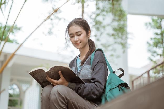 Porträt der glücklichen studentin, die das buch auf dem campushof liest