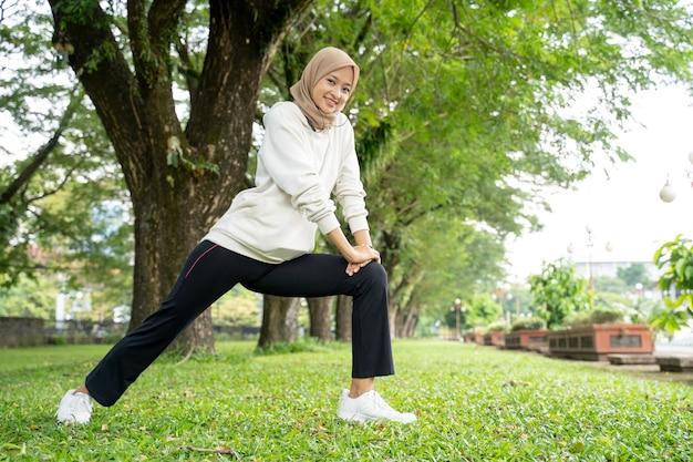 Porträt der glücklichen und lustigen muslimischen frau, die am morgen im freien trainiert
