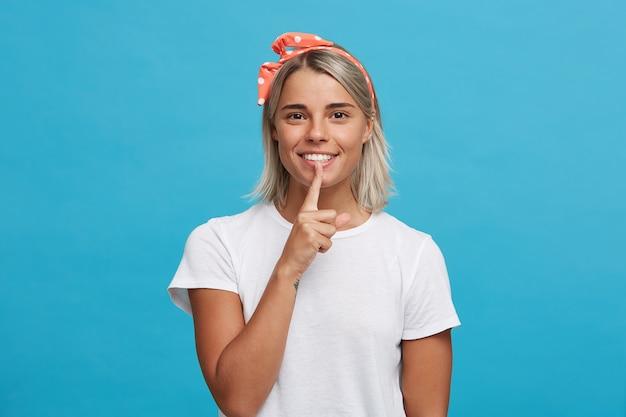 Porträt der glücklichen verspielten blonden jungen frau trägt weißes t-shirt