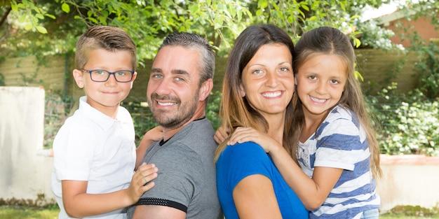 Porträt der glücklichen vierköpfiger familie im landschaftsgartenpark