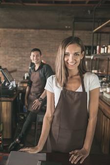 Porträt der glücklichen weiblichen kellnerin, die zur kamera und zu ihrem partner lächelt