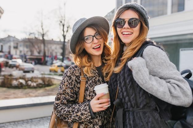 Porträt der glückseligen frauen, die zusammen am kalten morgen heraus hängen und draußen mit tasse kaffee posieren. erstaunliche junge frau im trendigen mantel und in der sonnenbrille, die zeit mit freund auf der hauptstraße verbringen.