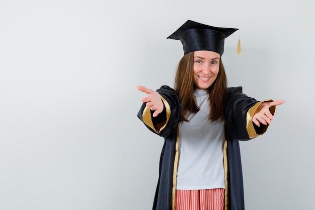 Porträt der graduierten frau, die arme für umarmung in der freizeitkleidung, in der uniform und in der fröhlichen vorderansicht öffnet