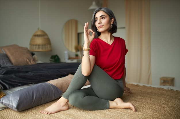 Porträt der grauhaarigen niedlichen jungen frau in der freizeitkleidung, die auf boden sitzt, ardha matsyendrasana tut oder halbe wirbelsäulendrehung sitzt, yoga praktiziert, verdauungssystem am morgen anregt