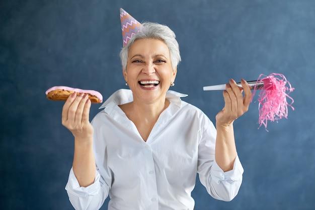 Porträt der grauhaarigen reifen frau mit rosa partyhut, der pfeife und eclair hält