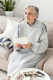 Porträt der großmutter, die auf der couch sitzt