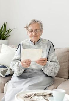 Porträt der großmutter, die bilder betrachtet