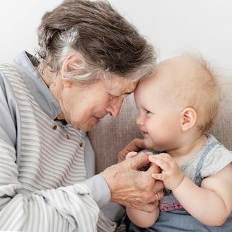 Porträt der großmutter, die das spielen mit baby umarmt