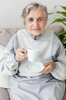 Porträt der großmutter, die kaffeetasse genießt