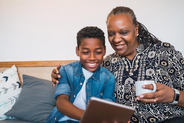 Porträt der großmutter und des enkels, die selfie mit digitalem tablett beim sitzen auf sofa couch zu hause nehmen. familien- und lifestyle-konzept.