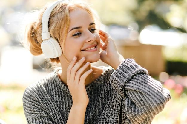 Porträt der grünäugigen rothaarigen frau, die musik im gewächshaus hörend aufwirft