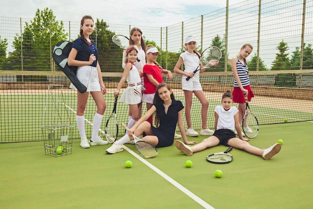 Porträt der gruppe von mädchen als tennisspieler, die tennisschläger gegen grünes gras des außenplatzes halten