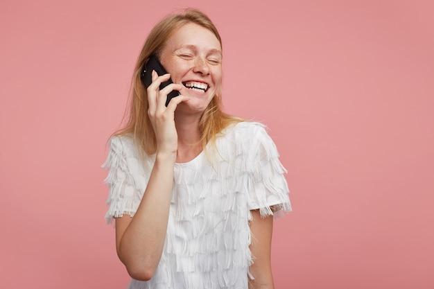 Porträt der gut aussehenden jungen glücklichen frau mit den foxy haaren, die smartphone in der erhöhten hand halten und fröhlich lächeln, während sie nette unterhaltung haben, lokalisiert über rosa hintergrund