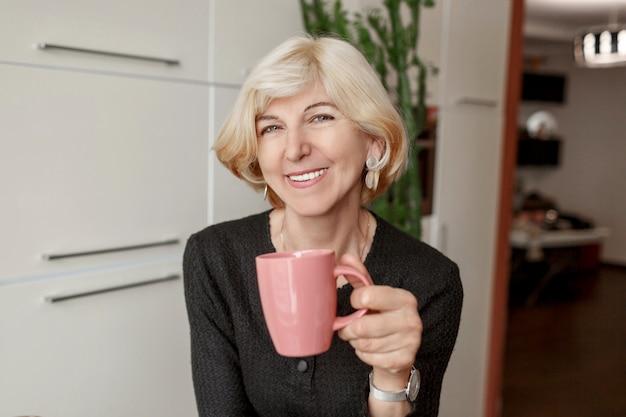 Porträt der gut aussehenden reifen gesunden schlanken frau mit tasse kaffee, die in ihrer modernen küche aufwirft