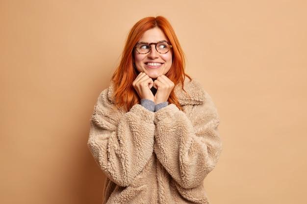 Porträt der gut aussehenden rothaarigen frau hält hände unter kinn schaut weg träumt glücklich von etwas in braunem mantel gekleidet.