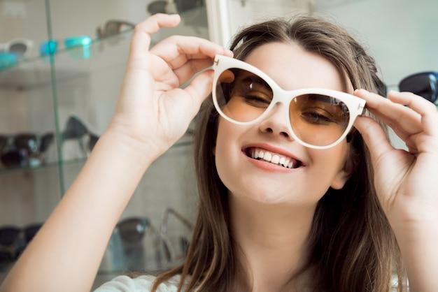 Porträt der gutaussehenden frau im optikergeschäft, das neues paar stilvolle sonnenbrillen auswählt