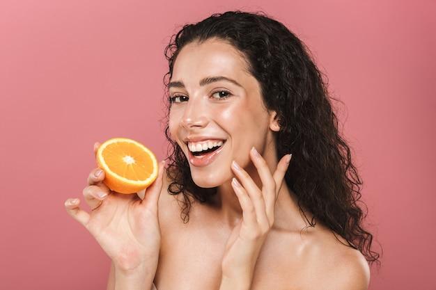 Porträt der halbnackten frau der brünetten mit dem langen haar, das lächelt und stück orange hält, lokalisiert über rosa hintergrund