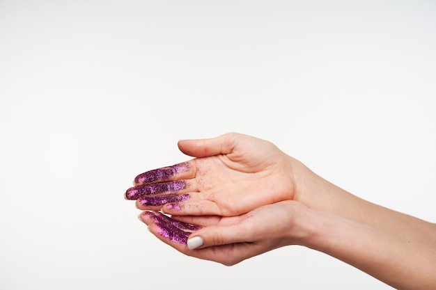 Porträt der hand der hübschen dame mit weißer maniküre, die palmen hochhält, während sie es vom funkeln wäscht, isoliert auf weiß