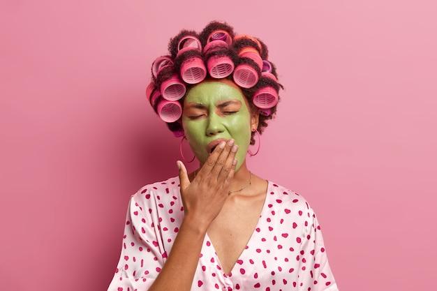 Porträt der hausfrau wacht am frühen morgen auf, hat schönheitsbehandlungen bedeckt mund und gähnen, trägt seidengewand trägt lockenwickler auf kopf isoliert über rosa. haarstyling, wellness-konzept