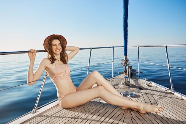 Porträt der heißen attraktiven erwachsenen frau, die auf dem bug der yacht sitzt und im bikini und im strohhut zwinkert. nettes sonnenbaden der frau, um während der ferien im ausland bessere bräune zu bekommen.