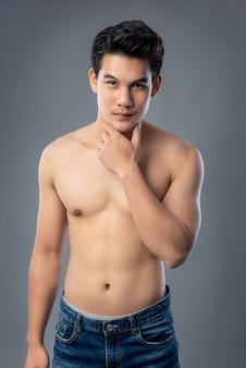 Porträt der hemdlosen jungen hübschen asiatischen mannstudioschuß