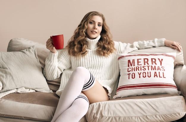 Porträt der herrlichen blonden frau im weißen wollpullover, der heißen kaffee im hellen gemütlichen dekorierten innenraum trinkt
