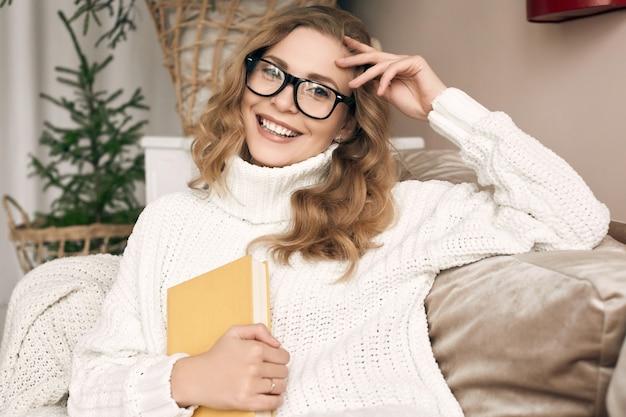 Porträt der herrlichen blonden frau im weißen wollpullover und im lesebuch der brille im hellen gemütlichen dekorierten innenraum