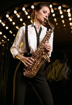 Porträt der herrlichen brünetten modellfrau im modischen formellen anzug mit saxophon
