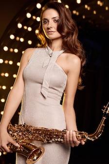 Porträt der herrlichen brünetten vorbildlichen frau im eleganten kleid mit saxophon