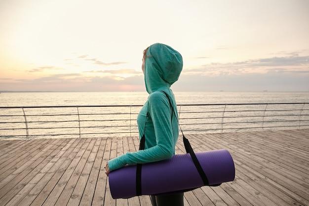 Porträt der herrlichen frau, die zum yoga praktiziert und sich am morgen streckt, sportkleidung trägt und am meer spazieren geht.