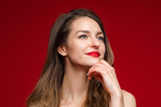 Porträt der herrlichen frau mit braunen haaren und roten lippen, die nachdenklich wegschauen und hand am kinn halten.