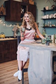 Porträt der herrlichen frau mit dem gewellten haar im rosa kleid, das ein glas champagner hält. weihnachten.