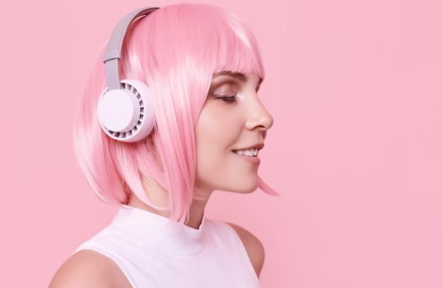 Porträt der herrlichen frau mit rosa haaren genießt die musik in kopfhörern