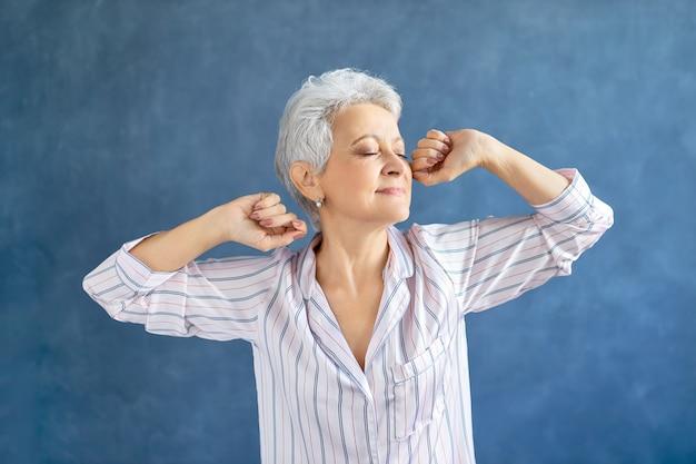 Porträt der herrlichen frau mittleren alters im stilvollen gestreiften pyjama, der körper streckt, nachdem er am frühen morgen erwacht