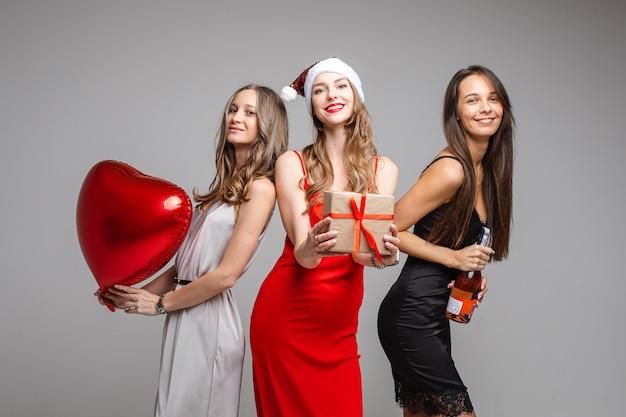 Porträt der herrlichen glücklichen damen in seidenkleidern mit rotem herzluftballon, geschenk und flasche roséwein, die spaß haben, auf grauer wand zu umarmen und aufzustellen