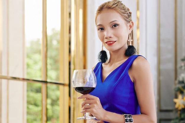 Porträt der herrlichen jungen asiatischen frau, die am fenster mit großem glas rotwein steht