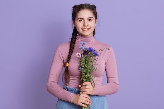 Porträt der herrlichen jungen brünetten frau mit langen haaren und zwei zöpfen, pullover und jeans tragend, blumenstrauß von feldblumen haltend, stehende isolierte lila wand stehend.