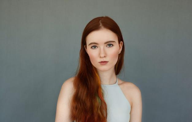 Porträt der herrlichen kaukasischen frau mit dem langen roten haar, das isoliert an der leeren grauen wand steht und ernstes aussehen hat und starrt. junge frau, die wehrlos aussieht. jugend, schönheit und mode