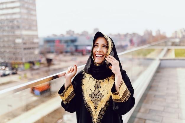 Porträt der herrlichen muslimischen frau gekleidet in der traditionellen kleidung unter verwendung des smartphones, während auf dem dach stehend.