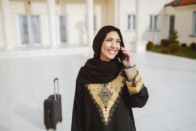 Porträt der herrlichen muslimischen frau in traditioneller kleidung unter verwendung des smartphones für das anrufen des taxis, während vor ihrem haus stehend. im hintergrundgepäck.