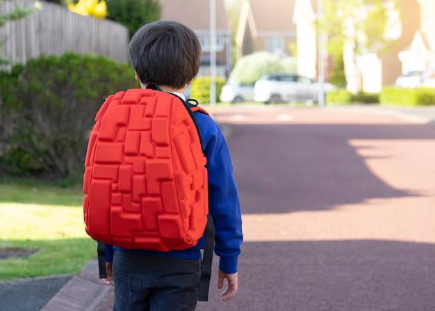 Porträt der hinteren ansicht des tragenden rucksacks des schuljungen, der zur schule geht