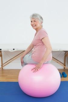 Porträt der hinteren ansicht einer älteren frau, die auf yogaball sitzt